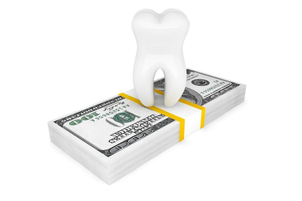 Midwest City OK Dental Financing | A tooth sits on top of a stack of cash
